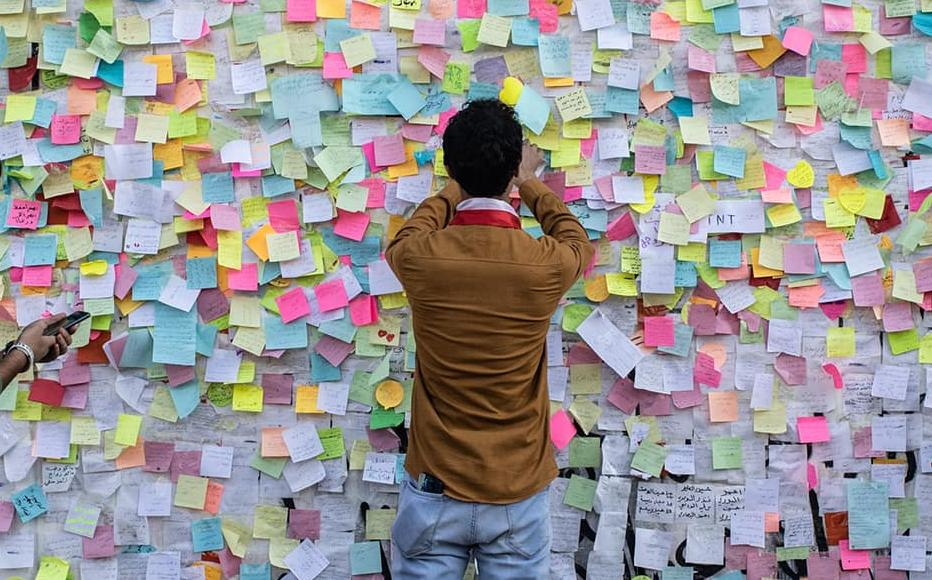 """Demonstrators paste wishes on post-it notes on the """"wish wall"""" in Tahrir Square on Nov. 22, 2019 in Baghdad, Iraq."""