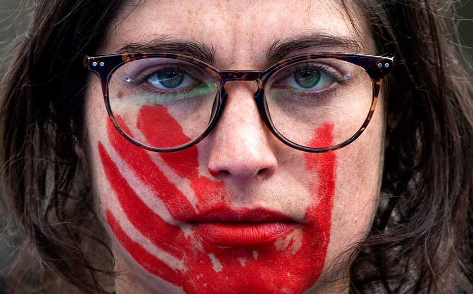 A woman wears red face paint depicting a hand during a protest during the International Women's Day in Madrid, Spain.
