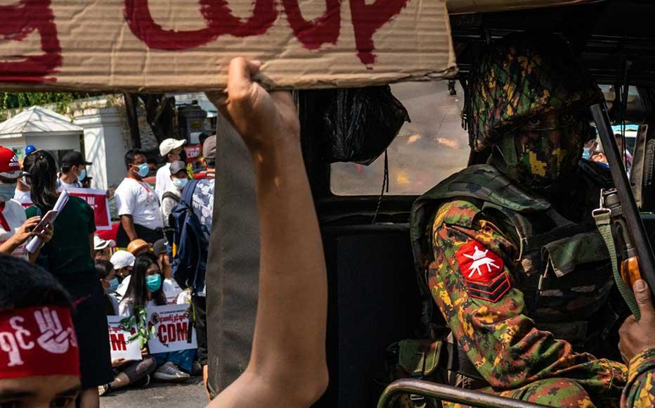 Protesters marching past Myanmar military soldiers who arrived to guard the Central Bank overnight on February 15, 2021 in Yangon, Myanmar.