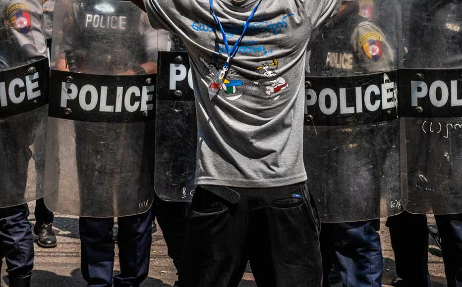 A resident stands in front of a line of riot police on February 25, 2021 in Yangon, Myanmar.