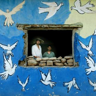 Northern Iraqi Kurds look out a window of their house adorned with doves June 16, 2003 in a village near Erbil, Iraq.
