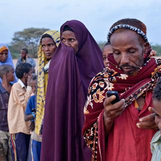 Sahal Gure Mohamed, 62, texts on his mobile phone while waiting in line at dawn to register at Ifo refugee camp in Dadaab, Kenya. (Photo: InternewsEurope/Flickr)